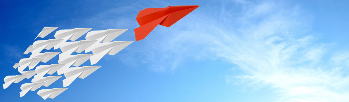 Group of paper airplanes against a blue sky, following one large red paper airplane